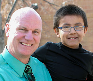 Mike poses outside with a male student at St. Joseph's Indian School in Chamberlain, South Dakota.