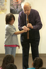 James shows Pearl, a third grader, where to place her fingers on the flute.