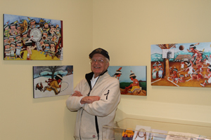 Peter Paul stands next to his many pieces of art.